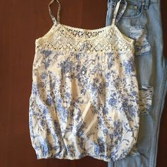 """Lovey floral pattern tank top Cute cream lightweight tank top with blue floral pattern. Top of the tank has lace and 6 decorative buttons. Straps are spaghetti straps that have been shortened--easily can be lengthened back to their original length--currently measure 4.5"""" bottom of the top is elastic. 100% cotton. Delias Tops Tank Tops"""