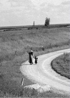 Gezicht op een weg in een kromming van de oostelijke Eemdijk bij Eemdijk (gemeente Bunschoten), uit het zuiden, met een vrouw en kind in klederdracht. 1948 WF van Heemskerck Düker (fotograaf) #Utrecht #Spakenburg