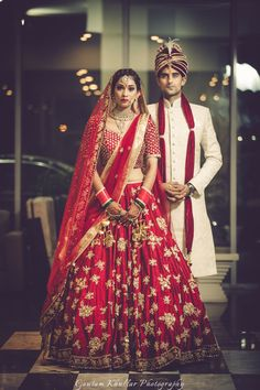 Bridal Wear - Bride in a Red Big Flare Lehenga | WedMeGood | Red Bridal Lehenga with Golden Embroidery and Double Dupatta, Groom in a Beige Sherwani with Red Safa #wedmegood #indianbride #indianwedding #lehenga #bridal #red #coupleshot #candidcouple