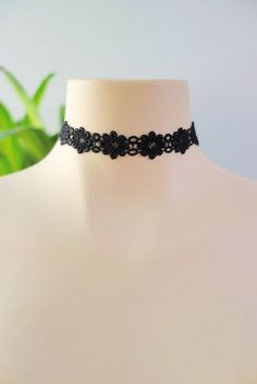 "This black choker features a thin crocheted band with a stylized daisy flower design. Finished with an adjustable lobster clasp closure at back for an adjustable fit. - Width .75"" - Length: 12"""