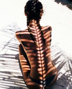 The shadow thrown by the palm branch is perfectly aligned with this woman's spinal column, for an eerie effect.
