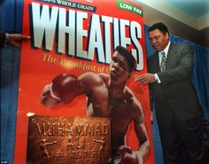 Muhammad Ali, known as 'The Greatest,' poses next to a Wheaties poster during the unveilin...