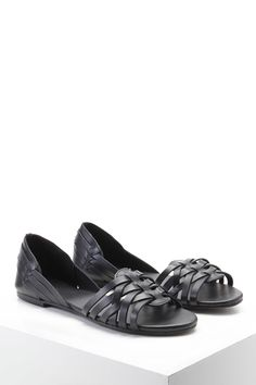 A pair of genuine leather slip-on sandals featuring an interwoven front and back design, an open toe, and cutout sides.