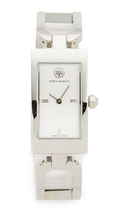 Geometric links form the polished band of this opulent Tory Burch watch. A petite logo accents the dial. Hinged-snap clasp. Scratch resistant. Swiss movement. Hardshell case and cleaning cloth included.