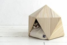 The Hokura Paulownia pet box by Natural Slow Inc. has a small triangular opening, making it a cave-like space for cats and small dogs.