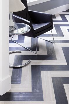 Chevron wood floors and glass side table beside modern armchair