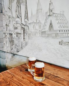 """Pin for Later: Say """"Espresso Patronum"""" (or Butterbeer!) at This Magical Harry Potter Cafe There's a detailed mural of Hogsmeade village on one of The Nook's walls."""