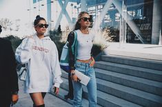 Romee Strijd and Taylor Hill street style wearing an oversized sweatshirt and boots, and a T-shirt and jeans outfit with a duster jacket