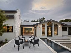 roof, black trim windows, stone, white stucco