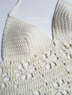 Floral Bikini Top by Carolyn Calderon. The Floral Bikini Top is perfect for warm weather. Made with cotton yarn and a pretty floral design, this pattern includes three sizes that you can interchange the bikini cups and the floral edging so you can get a custom and flattering fit. Worn as a bikini top or layered, it's a fabulous addition to your wardrobe. #crochetpattern #thepurpleponcho #crochetbikinitop #crochetlace
