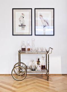 Retro und doch so modern! Eine Hausbar ist das Interior Must-have in Eurem Zuhause. Schnappt Euch einen Barwagen beispielsweise in Gold und dekoriert ihn mit klaren Kristallgläsern, Spirituosen und dezenten Accessoires. Fertig ist ein glamouröser und zeitloser Hausbar Look! // Hausbar Deko Barwagen Dekorieren Servierwagen Bar Cart Styling Cocktails Teewagen