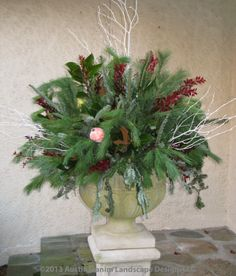 Williamsburg style holiday decor.  White pine and fraser fir boughs are used in conjunction with evergreen magnolia, white birches, and red ruscus to offset the decorative fruit ornaments.