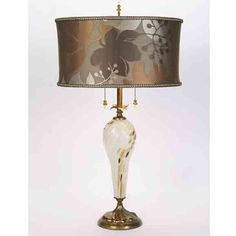 Kinzig Pearl table lamp 77af80 has a smoky silver hand blown glass base, with metallic accents, and an oval shade with a large floral print in bronze, copper, pewter, and cream colors. Engraved signature on bottom. Glass bead pulls and finial. Handmade in the USA. http://www.sweetheartgallery.com/collections/kinzig-design-table-lamps-artistic-artisan-designer-table-lamps