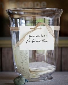 Hurricane Vase Guest Book - A large hurricane vase from IKEA was displayed with stacks of rubber-stamped cards for guests to write their well wishes on. Stones from the nearby beach weighted down the cards.