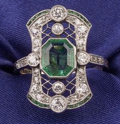 Art Deco Emerald, and Diamond Ring, centering a bezel-set step-cut emerald measuring 7.70 x 6.45 x 3.40 mm, bead and bezel-set with old European and single-cut diamonds, edged with channel-set emeralds, engraved gallery, platinum-topped 18kt gold mount, size 6. Skinner.