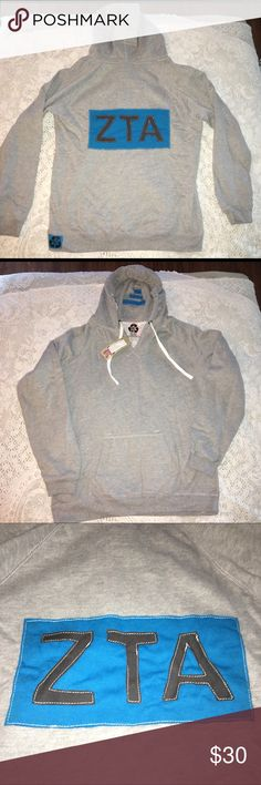 NWT Zeta Tau Alpha sorority gray hoodie AL. ZTA NWT Zeta Tau Alpha ZTA gray & teal hoodie pull over. Size AL. 60% poly 40% cotton.  V neck, draw string in good, logo appliqué on back & solid front. Front kangaroo pockets. Made in USA. $62 retail. Rare and one of a kind. #greek #life #college #university #zeta #tau #alpha #sorority #pledge #teal #black #big #little #sister #nwt #hoodie #vneck Never used. Smoke free home. Check closet for similar items & additional sororities. ❌no trades❌…