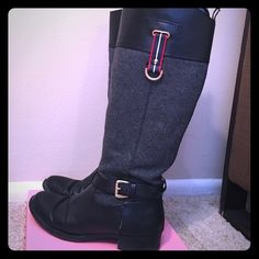 "Tommy Hilfiger Tall Boots Tommy Hilfiger Tall Boots, Black Leather on the top and bottom of the boot, along with a buckle on the outside of each boot. there is a red, navy blue and white strap with a gold loop at the end saying ""Tommy Hilfiger"". In between the top and bottom leather there is gray fabric. the back of the boot has a leather strap going up with a loop at the top. It zippers on the inside calf of the boot. on the inside of the boot there is a plaid pattern. Size 7 1/2. Tommy…"