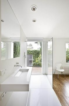 A bright, white bathroom. Shower head as a support.    A work of Maria Castello Martinez, a great spanish architect with a very consistent, well designed and beautifully minimal portfolio.