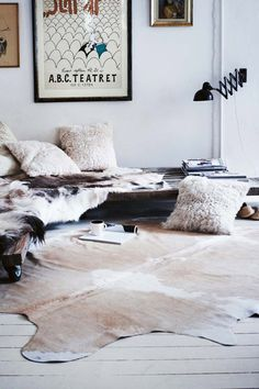 white walls cowhide rug fur pillows