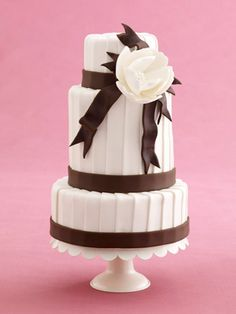 """theknot.com, cake bliss in Brooklyn, NY, a chocolate brown and white wedding cake, I like the """"pleats"""" and the bold focus to the single flower and the chocolate """"ribbons."""""""