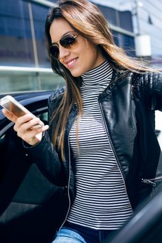 Beautiful young woman using her mobile phone in the car. Free Photo