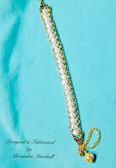 """Gold is a pearl's best friend! We love this 14K gold overlaid on brass rolo chain and white freshwater pearl bracelet with hand made bobble charm by Alexandra Marshall. 7 1/2"""" with magnetic clasp & security chain. $59. #B1927. To order double click on photo."""