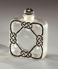 RENE LALIQUE (1860-1945) pour FORVIL Flacon de parfum «Les cinq fleurs» de forme carrée à angles arrondis, en verre blanc soufflé-moulé à décor d'entrelacs émaillés noir. Signé «R.Lalique France». #chanel style
