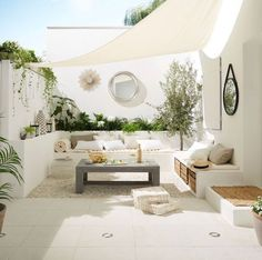 Shade sail over all white garden seating