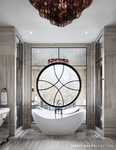 A freestanding tub placed under a round window that's tucked in the center of a mirror is a swoon-worthy feature. | Designer: Ferris Rafauli
