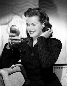 Janis Paige sitting on a Couch in Black Long Sleeve Velvet Dress with – Movie Star News