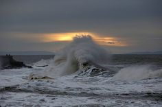 Storm-tossed waves roll in to shore and break along the seafront at Porthcawl, Wales