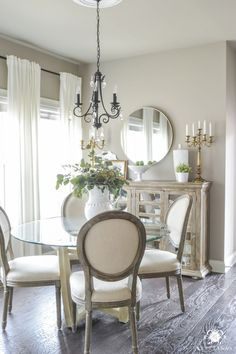 Updated Breakfast Nook- A Lighter, Brighter Look - Kelley Nan Round Brass Mirror over Buffet with Candelabras. White Ikea Ritva Curtains and Round Back Paige Dining Chairs. Perfect Greige Sherwin Williams Paint and Dark Floors