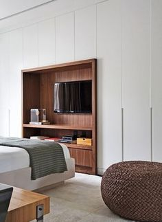 Quarto do casal. Em meio aos armários brancos, um nicho de nogueira-americana posiciona a TV diante da cama. Pufe da Codex Home e tapete da By Kamy (Foto: Denilson Machado / MCA Estúdio / Divulgação)