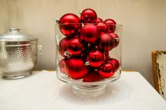 How to stage your home for a holiday party: Display ornaments in an extra wide vase and pile over the top