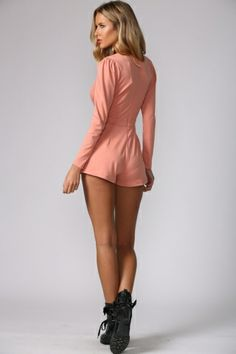 Long-sleeved peach playsuit. Plunging V neckline to waist. Invisible back zip.  Slightly frilly shorts hems.  Polyester.