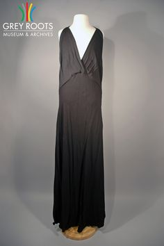 A black, halter-style dress which would have been worn with a matching sequined bolero jacket (not pictured). The dress was made by Frances Kaye Frocks - Paris. The dress is unlined and made of a rayon crepe fabric. Grey Roots Museum & Archives Collection.