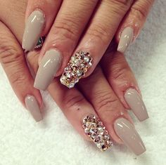 Tan nails with white and yellow Swarovski crystals.