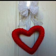 Cardboard from a diaper box cut into a heart + red yarn + leftover ribbon from Christmas = happy Valentine's door.