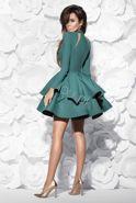 Rozkloszowana sukienka z długim rękawkiem z wycięciami pokrytymi cielistąsiateczką. Tkanina jest elastyczna dzięki temu dobrze dopasowuje siędo sylwetki. Dół sukienki usztywniany tiulem. Z tyłu zapinana na kryty zamek.