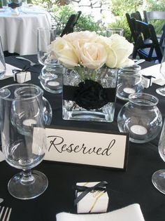 love the white floral centerpiece with black ribbon
