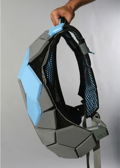 the bag is constructed from rugged geometric polygonal shapes that harness the tension of the elastic fabrics, which is gained by attaching the rugged parts to the while they are stretched on a frame.
