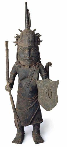 Este guerrero se presenta en las vestiduras de Oba Esigie. Lleva la gorra típica coral, coral gargantilla, faja-como collar de coral a través de la parte superior del cuerpo envolvente falda con apéndice rígido en poder de una máscara de marfil, la lanza y el escudo.