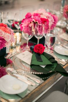 Each guest's place setting featured a silver-beaded charger plate topped with a forest green linen napkin and a floret in cerise. Mirrored tables featured low centerpieces composed of roses in shades of pink. #centerpiece #placesetting Photography: Troy Grover Photographers. Read More: http://www.insideweddings.com/weddings/jet-setter-couples-modern-wedding-with-travel-inspired-elements/528/
