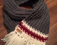 Un bonnet aux couleurs typiques des bas de laine chauds et réconfortants. Crème, rouge et gris, ses couleurs sagencent avec tout. Il est complété par un pompon doux de fausse fourrure de raton laveur. Fait sur mesure, il fera à toutes les têtes. Il est également possible de se procurer le bonnet sans pompon ou encore avec un pompon de laine beige, grise ou rouge.
