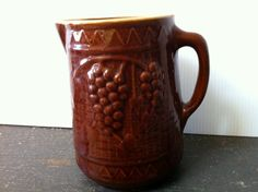 Vintage Brown Pitcher with a high glaze.  Star on bottom.  Grape Design, Yellow Ware type finish inside.