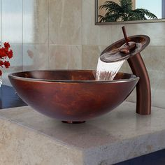 Turn your bathroom into an exotic oasis when you add this glass vessel sink and waterfall faucet to your decor. The abstract design and brown and gold tones in the glass guarantee this sink and faucet will be a treasured conversation piece.