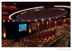 "Queen Mary 2 Illuminations theater. (Photo: Mark Lawton) The ship's 500-seat theater can be converted into a 150-seat planetarium. The circle on the ceiling is where the dome is and the red seats beneath it not only recline, but also get 360 degree views when the planetarium is in use. ©Mona Evans, ""Illuminations - A Planetarium Afloat"" http://www.bellaonline.com/articles/art21354.asp"