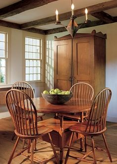 FARMHOUSE – INTERIOR – vintage early american farmhouse showcases raised panel walls, barn wood floor, exposed beamed ceiling, and a simple style for moulding and trim, like in this farmhouse dining room.