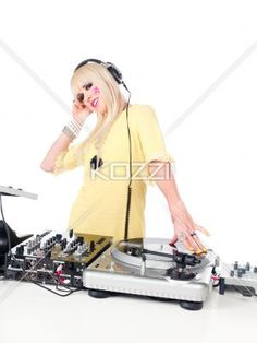 portrait of a young female with headphone behind a dj mixture. - Portrait of a happy young attractive female with headphones behind a Dj mixing machine over plain white background.