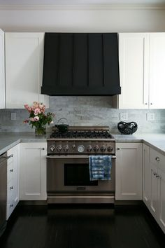 The simple, chic kitchen features clean white cabinets with graphic black accents and a Japanese lacquer bowl from MARCH. Lauren indigo dyed the shibori tea towels herself | archdigest.com